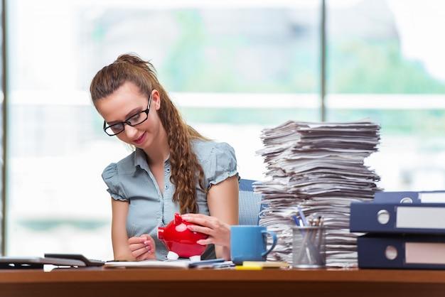 Młody bizneswoman z prosiątko bankiem w biurze
