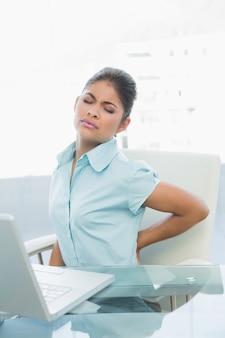 Młody bizneswomanu cierpienie od tylnej obolałości wewnątrz w biurze