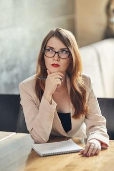 Młody bizneswomanu główkowanie z notatnikiem