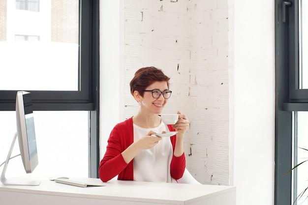 Młody bizneswomanu obsiadanie na biurku z filiżanką kawy przy stołem z ekranem komputerowym.