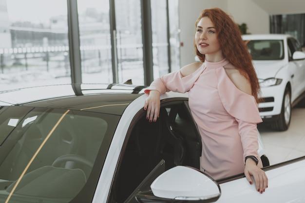 Młody bizneswomanu zakupy dla nowego samochodu przy przedstawicielstwo handlowe sala wystawową