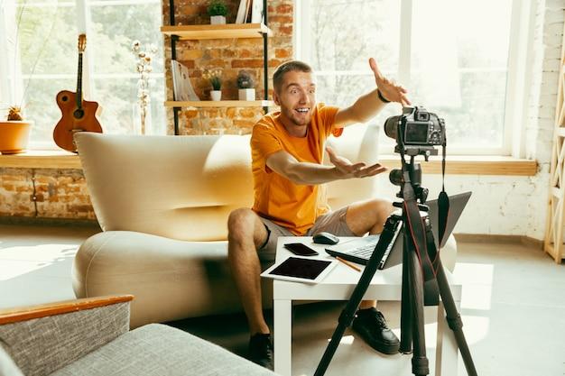 Młody bloger kaukaski z profesjonalnym aparatem nagrywającym wideo przegląd gadżetów w domu. blogowanie, videoblog, vlogowanie. mężczyzna nagrywający vloga lub transmitujący na żywo zdjęcia lub nowinki techniczne.