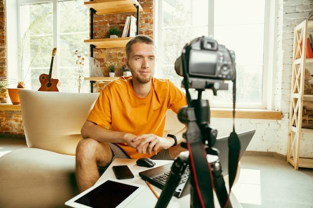 Młody bloger kaukaski z profesjonalnym aparatem nagrywającym wideo przegląd gadżetów w domu. blogowanie, videoblog, vlogowanie. mężczyzna tworzy vloga lub transmituje na żywo zdjęcia lub nowinki techniczne.