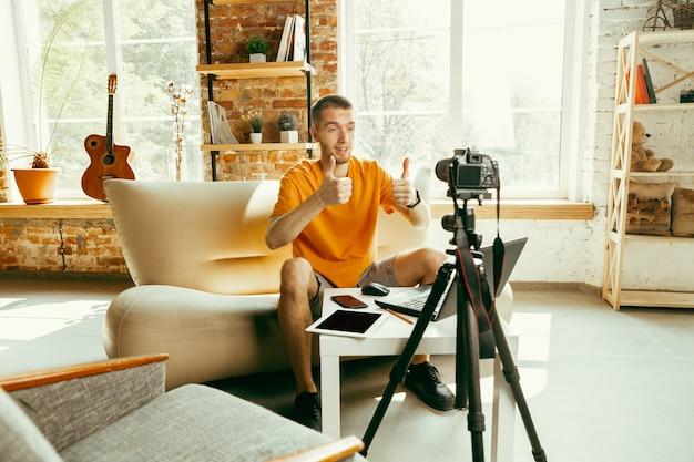 Młody bloger kaukaski z profesjonalnym aparatem nagrywającym wideo przegląd gadżetów w domu