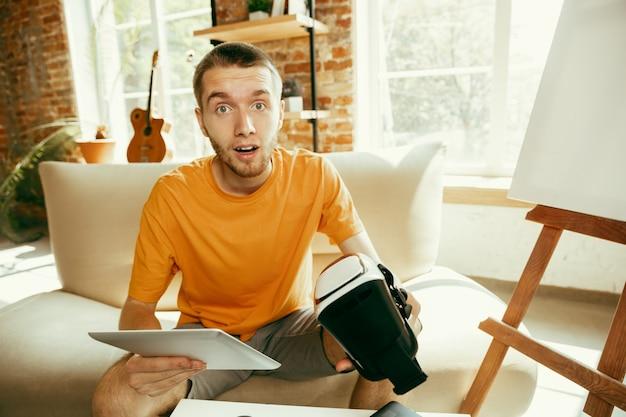 Młody bloger kaukaski z profesjonalnym sprzętem nagrywający w domu przegląd wideo okularów vr. blogowanie, videoblog, vlogowanie. mężczyzna nagrywający vloga lub transmitujący na żywo zdjęcia lub nowinki techniczne.