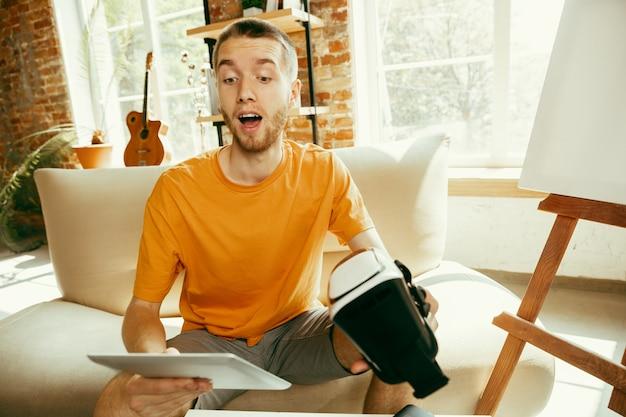 Młody bloger kaukaski z profesjonalnym sprzętem nagrywający w domu przegląd wideo okularów vr