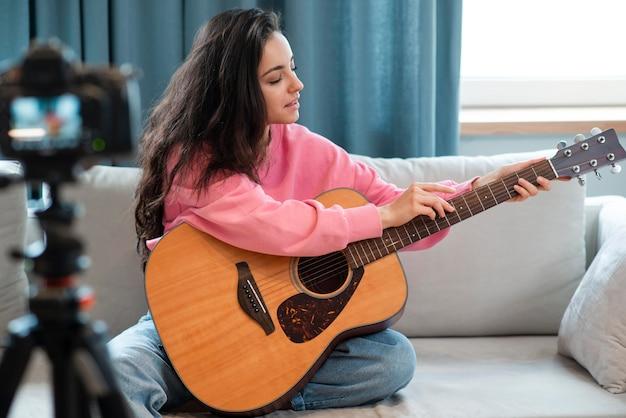 Młody bloger pokazujący, jak umieścić palce na gitarze