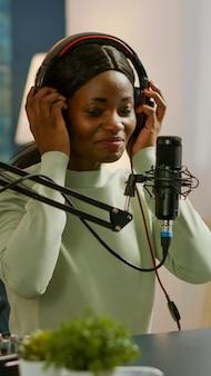 Młody bloger uśmiechający się do publiczności podczas kręcenia podcastu