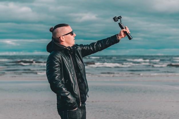Młody bloger w okularach przeciwsłonecznych robi selfie lub przesyła strumieniowo wideo na plaży przy użyciu kamery sportowej ze stabilizatorem aparatu z gimbalem.