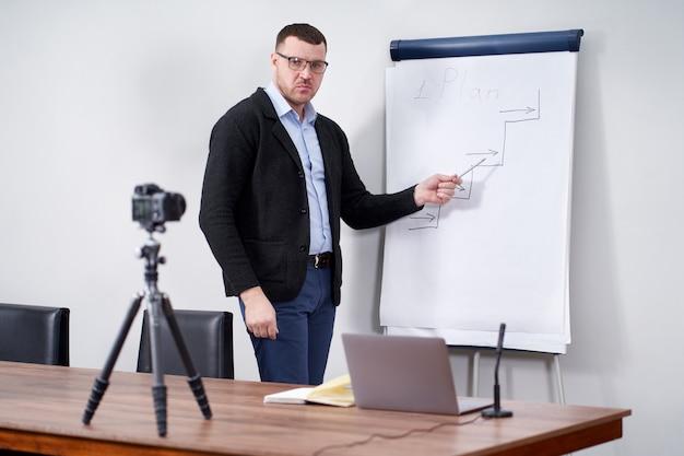 Młody bloger wideo prezentujący ważne dane na temat flipchartu, koncepcji edukacji online