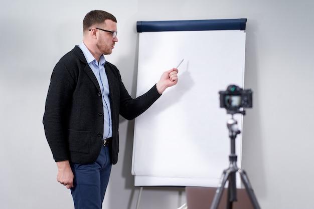 Młody bloger wideo prezentujący ważne dane na temat pustego makieta flipchart, koncepcja edukacji online