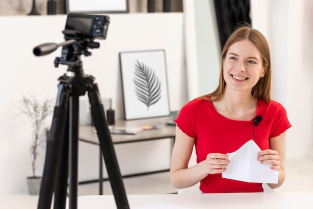 Młody blogger uśmiecha się i trzyma papier