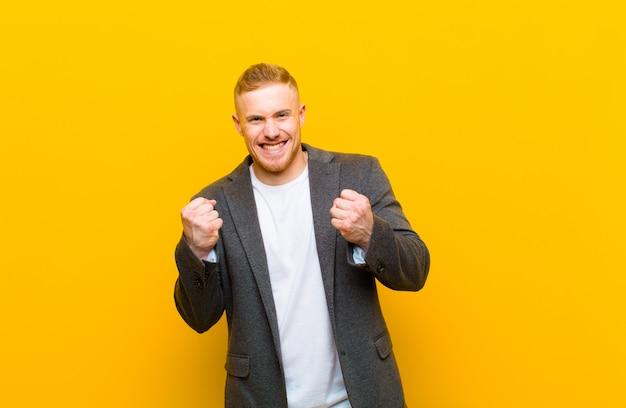 Młody blond biznesmen krzyczy triumfalnie, śmiejąc się i czując się szczęśliwy i podekscytowany, świętując sukces