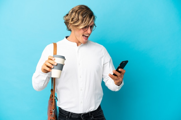 Młody blond biznesmen na niebieskim tle trzyma kawę na wynos i telefon komórkowy and