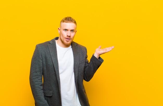 Młody blond biznesmen wyglądający na zaskoczonego i zszokowanego, z opuszczoną szczęką, trzymający przedmiot z otwartą dłonią na boku