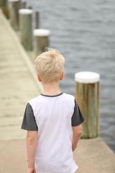 Młody blond chłopiec chodzący po drewnianym molo
