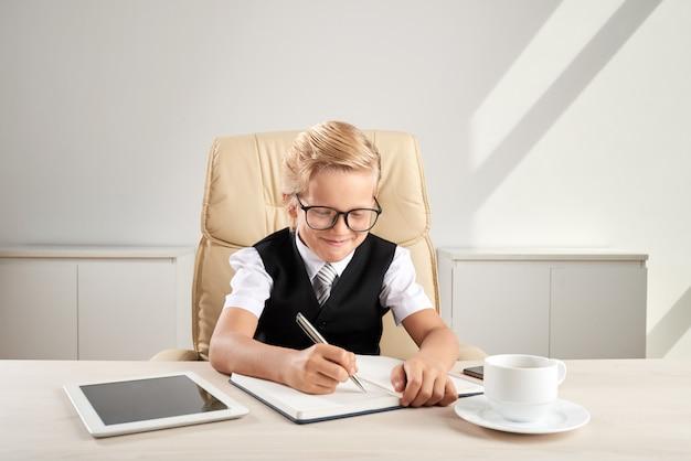 Młody blond chłopiec rasy białej siedzi na krześle wykonawczym w biurze i pisze w dzienniku