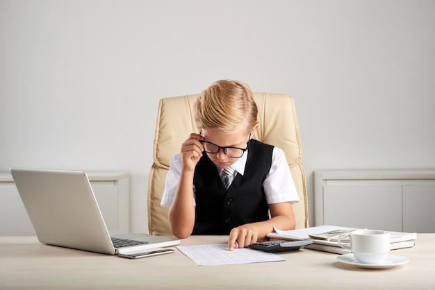 Młody blond chłopiec rasy białej siedzi przy biurku w biurze i studiuje dokumenty