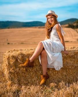 Młody blond kaukaski rolnik w białej sukni i białym kapeluszu w letnie popołudnie