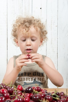 Młody blond kędzierzawy chłopiec je wiśnie
