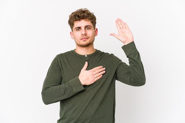 Młody blond kręcone włosy kaukaski mężczyzna na białym tle biorąc przysięgę, kładąc rękę na klatce piersiowej.