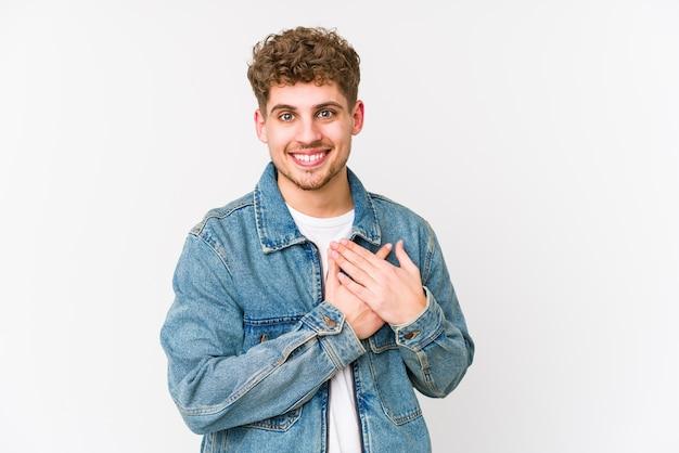 Młody blond kręcone włosy kaukaski mężczyzna na białym tle ma przyjazny wyraz, przyciskając dłoń do piersi.