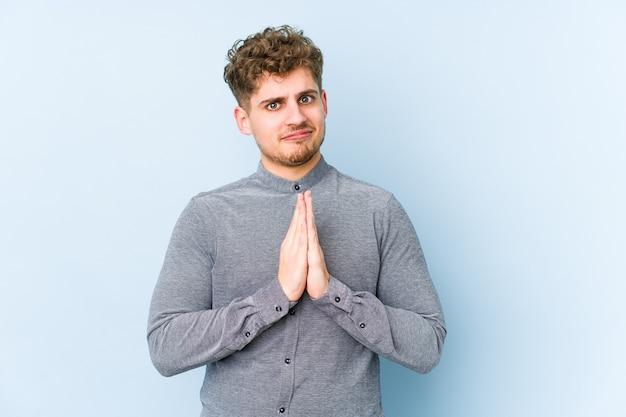 Młody blond kręcone włosy kaukaski mężczyzna na białym tle modląc się, okazując oddanie, osoba religijna szuka boskiej inspiracji.