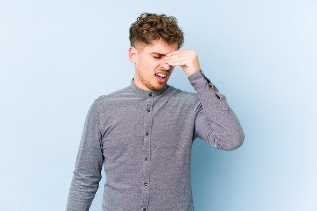 Młody blond kręcone włosy kaukaski mężczyzna na białym tle o ból głowy, dotykając przodu twarzy.