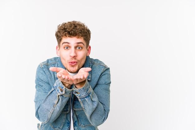 Młody blond kręcone włosy kaukaski mężczyzna na białym tle składane usta i trzymając dłonie, aby wysłać pocałunek w powietrzu.