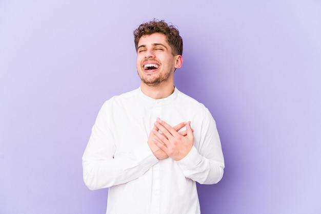 Młody blond kręcone włosy kaukaski mężczyzna na białym tle śmiejąc się trzymając ręce na sercu, pojęcie szczęścia.