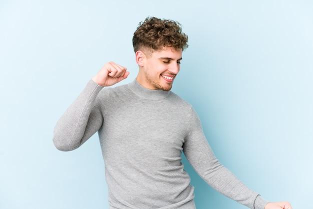 Młody blond kręcone włosy kaukaski mężczyzna na białym tle, taniec i zabawę.
