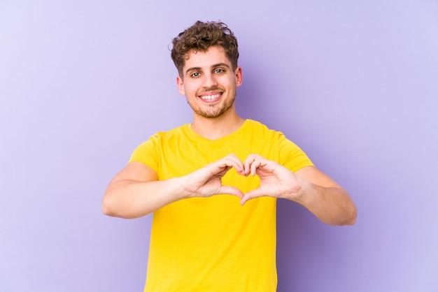 Młody blond kręcone włosy kaukaski mężczyzna na białym tle uśmiechając się i pokazując kształt serca rękami.
