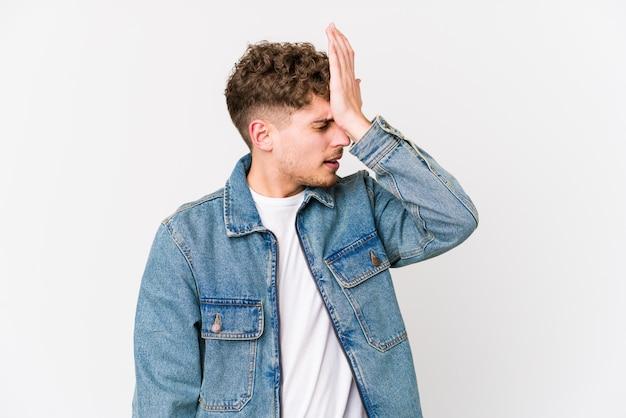Młody blond kręcone włosy kaukaski mężczyzna na białym tle zapominając coś, uderzając dłonią w czoło i zamykając oczy.