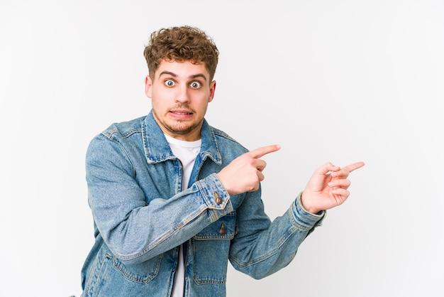 Młody blond kręcone włosy kaukaski mężczyzna na białym tle zszokowany, wskazując palcami wskazującymi na miejsce.