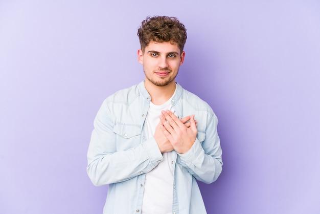 Młody blond kręcone włosy na białym tle kaukaski mężczyzna ma przyjazny wyraz, naciskając dłoń na piersi. koncepcja miłości.