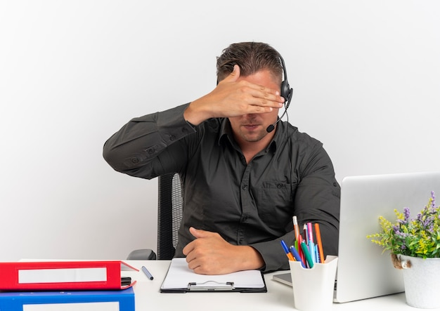 Młody blond pracownik biurowy mężczyzna na słuchawkach siedzi przy biurku z narzędziami biurowymi za pomocą laptopa ukrywa twarz ręką odizolowaną na białym tle z miejsca na kopię