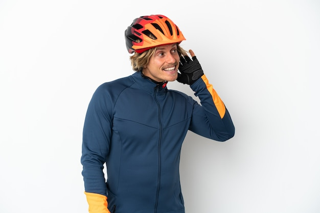 Młody blond rowerzysta mężczyzna na białym tle słuchając czegoś, kładąc rękę na uchu