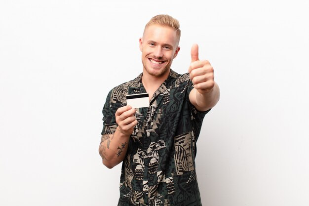 Młody blondyn czuje się dumny, beztroski, pewny siebie i szczęśliwy, uśmiechając się pozytywnie kciukami do góry z kartą kredytową
