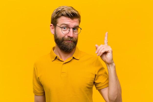 Młody blondyn czuje się jak geniusz, który dumnie unosi palec w powietrzu po zrealizowaniu świetnego pomysłu, mówiąc eurekę o pomarańczową ścianę