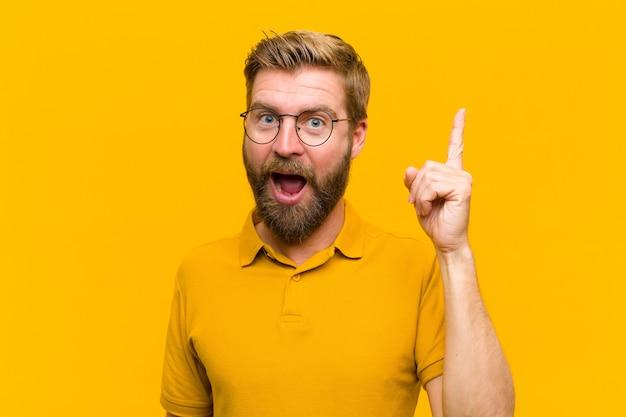 Młody blondyn czuje się jak szczęśliwy i podekscytowany geniusz po zrealizowaniu pomysłu, radośnie podnosząc palec, eureka! o pomarańczową ścianę
