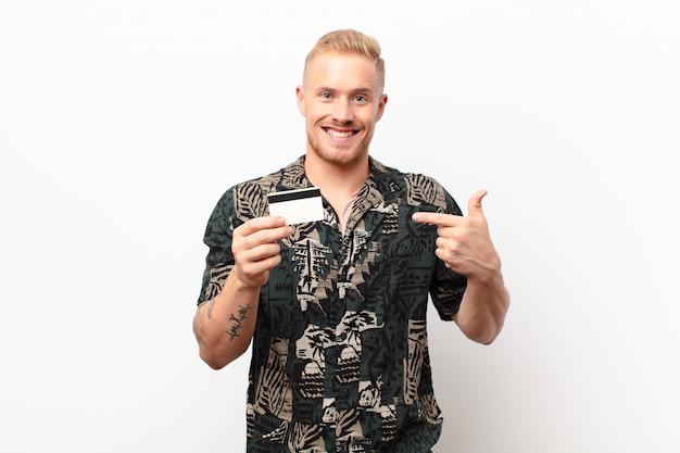 Młody blondyn czuje się szczęśliwy, zaskoczony i dumny, wskazując na siebie z podekscytowanym, zdumionym spojrzeniem z kartą kredytową