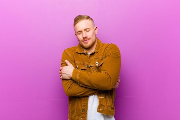 Młody blondyn czuje się zakochany, uśmiechając się, przytulając i tuląc siebie, pozostając singlem, będąc samolubnym i egocentrycznym na fioletowej ścianie
