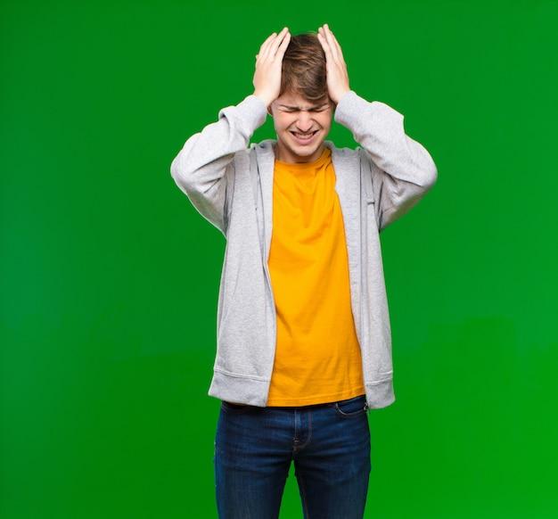Młody blondyn czuje się zestresowany i niespokojny, przygnębiony i sfrustrowany bólem głowy, podnosząc obie ręce do głowy na ścianie z kluczem chrominancji