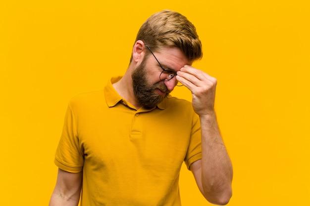 Młody blondyn czuje się zestresowany, niezadowolony i sfrustrowany, dotyka czoła i cierpi na migrenę silnego bólu głowy