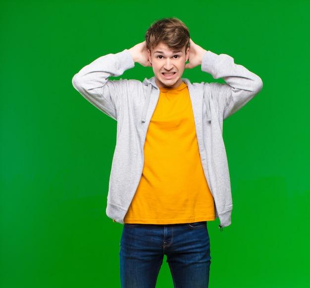 Młody blondyn czuje się zestresowany, zmartwiony, niespokojny lub przestraszony, z rękami na głowie, panikując w błędzie o ścianę klucza chrominancji