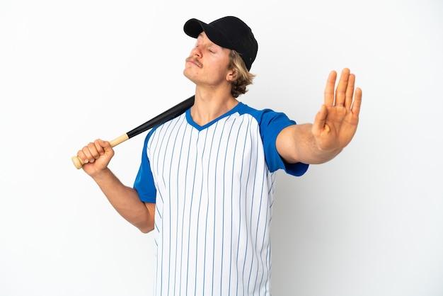 Młody blondyn gra w baseball na białym tle robi gest stop i rozczarowany
