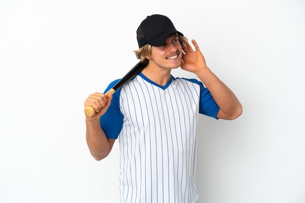 Młody blondyn gra w baseball na białym tle, słuchając czegoś, kładąc rękę na uchu