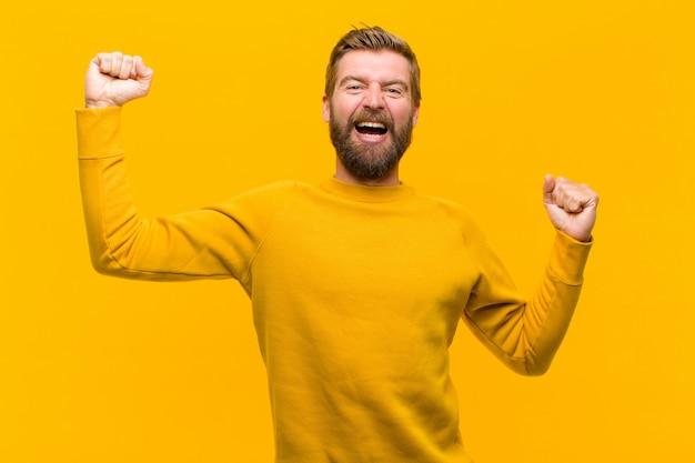 Młody blondyn krzyczy triumfalnie, wyglądając jak podekscytowany, szczęśliwy i zaskoczony zwycięzca, świętujący przy pomarańczowej ścianie