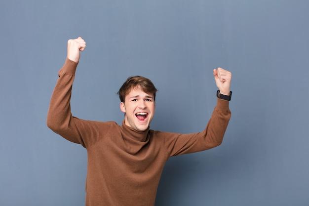 Młody blondyn krzyczy triumfalnie, wyglądając jak podekscytowany, szczęśliwy i zaskoczony zwycięzca, świętuje odizolowane na płaskiej ścianie