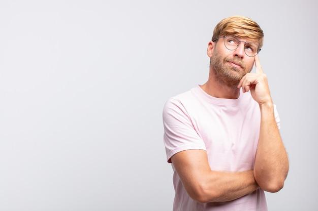 Młody blondyn myśli lub wątpi wyraz twarzy